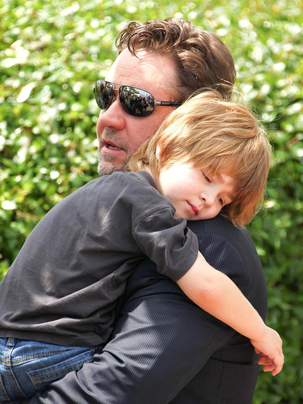 Actor Russell Crowe carries his son Tennyson Crowe at the *Robin Hood* photo call in 2010.