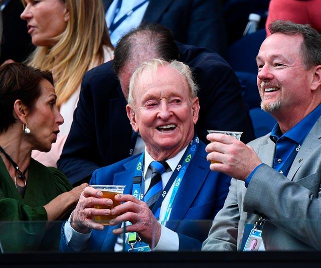 Aussie tennis legend Rod Laver was snapped watching the game he conquered with a cheeky beverage.