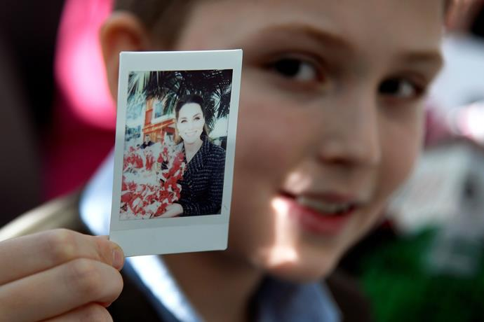 A very royal keepsake! Young Luke proudly presents his one-of-a-kind snap of the Duchess.