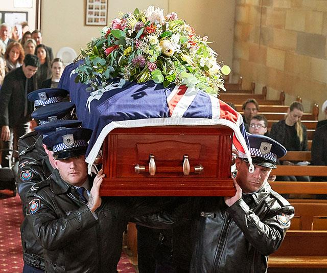Officers carry the former policeman to his final resting place.