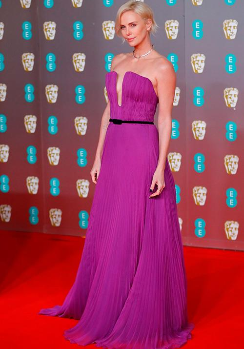 Charlize Theron clashed wonderfully with the carpet's red in this floor-length purple Dior dress.