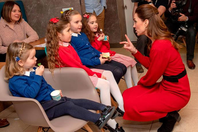 Underneath, the Duchess was wearing a beautiful red Zara dress, accessorised with a black belt.