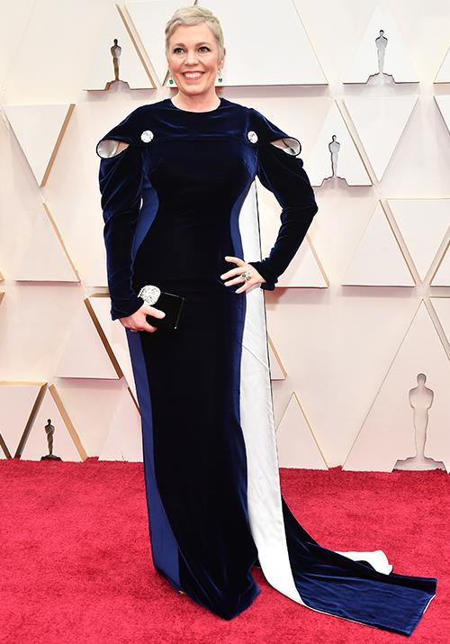 Olivia Colman opted for a unique blue, black and white gown. She subtly echoed her regal role on *The Crown* with those majestic bold shoulders...