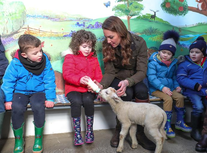 The Duchess helped children at the event feed a little lamb.