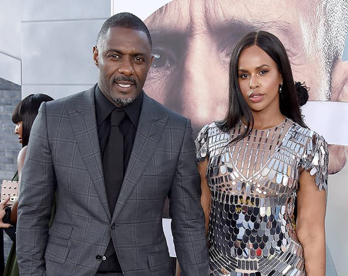 Idris Elba, pictured with his wife, says he is feeling OK and not presenting with any symptoms.