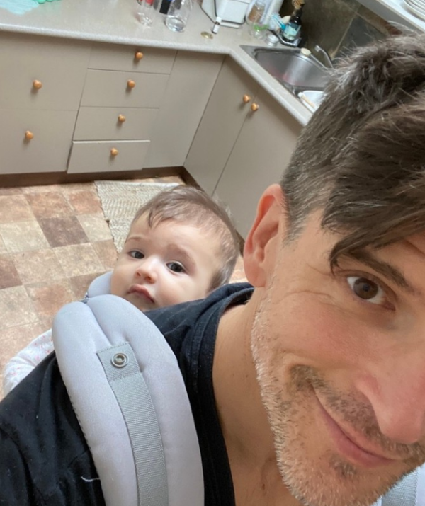 """Osher proves the """"baby in backpack look"""" is the ultimate adorable dad accessory with this kitchen seflie."""