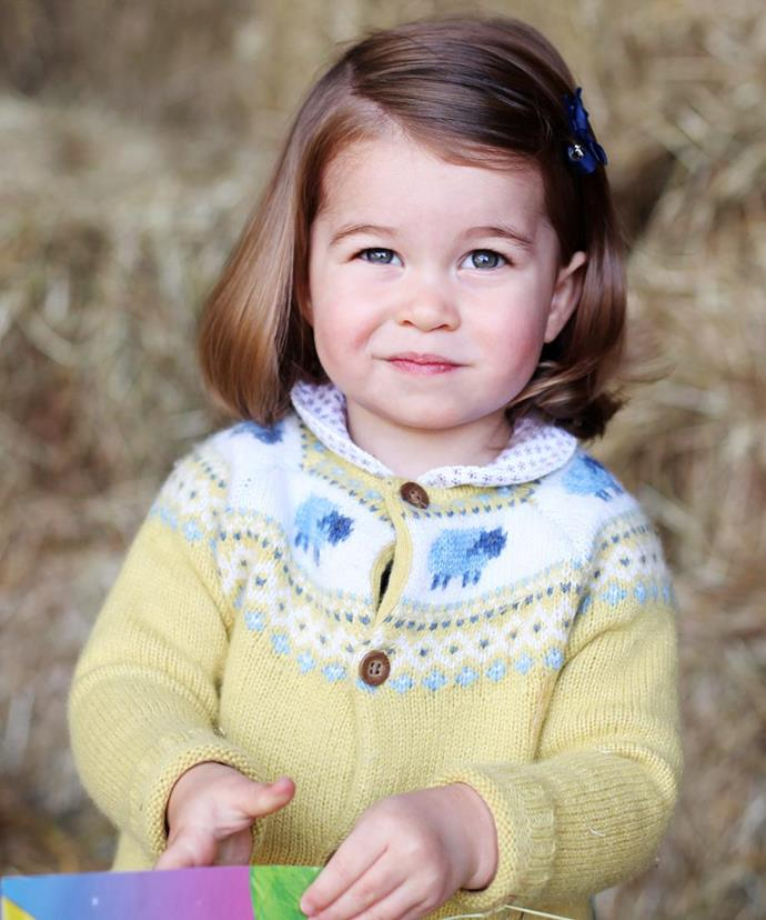 Princess Charlotte poses on a bale of hay at Anmer Hall on her second birthday back in 2017.