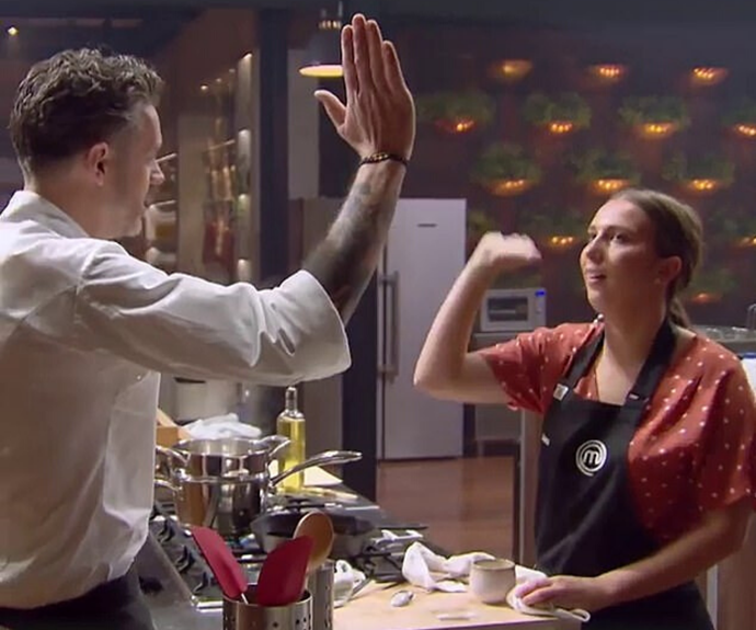 Laura and Jock sharing a high-five in the *MasterChef* kitchen.
