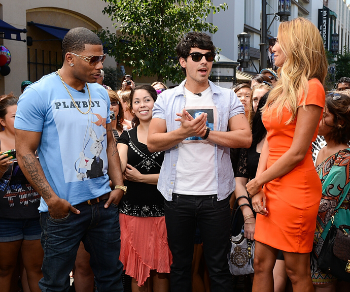 Renee (right) interviewing Joe Jonas and rapper Nelly (left) in 2012 on *Extra* in Los Angeles.