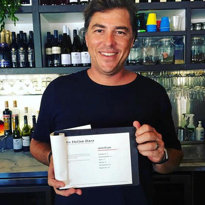 Pete pictured holding the menu of his cafe, The Italian Diner.