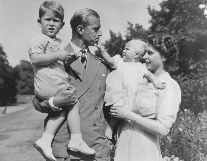 Then-Princess Elizabeth holds a baby Princess Anne as she walks the grounds of Clarence House with Philip, who holds Prince Charles, in 1951.