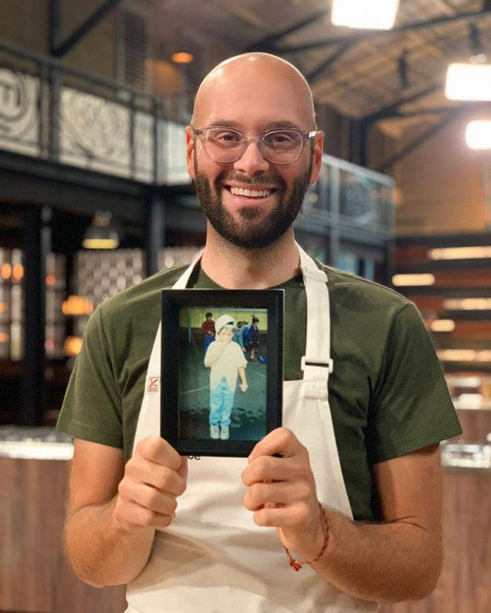 Reese holding a throwback photo of himself as a young boy, in the *MasterChef* kitchen.