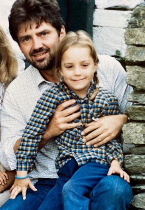 In the second snap, a young Kate (who looks remarkably like Louis in this snap!) sits on her father, Michael's knee.