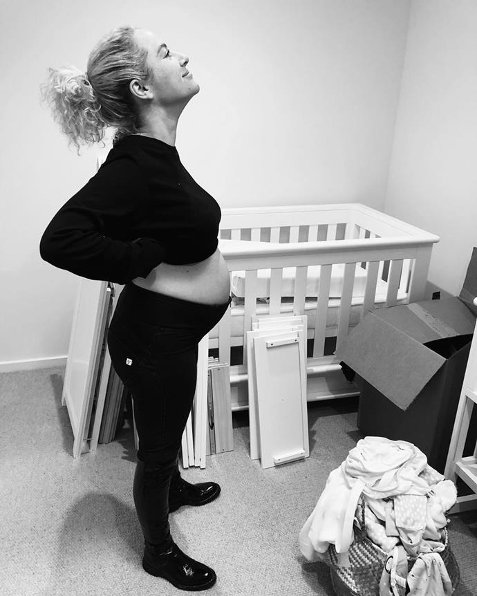 Ash and her pregnant belly preparing to set up her baby's nursery.