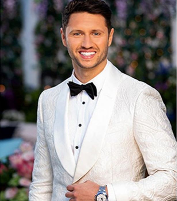 """**Damien Stone**<br><br>  Handsome, blue-eyed property valuer Damien instantly captured fans attention as he arrived in a white tux in the first trailer.<br><br> Charismatic, honest and fun-loving, he enjoys kicking back with the boys and relaxing in front of a romantic comedy with a glass of wine. <br><br> """"I'm a big fan of rom-coms. I grew up with two little sisters, so they were always on,"""" he says."""