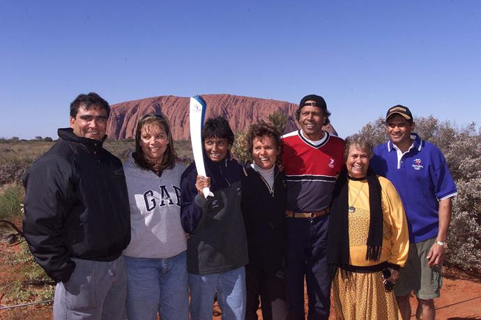 Lowitja (second from right) with Nicola Severino, Nova Peris-Kneebone, Evonne Cawley, Ernie Dingo, and Nicky Winmar, holding the Australian 2000 Olympic torch at Uluru, June 7, 2000.
