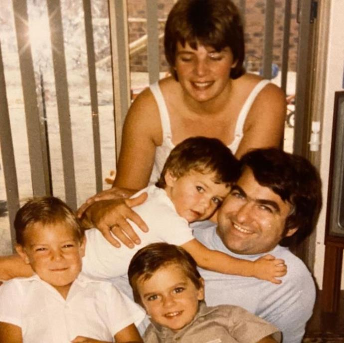A young Ant hugs his dad surrounded by his family.
