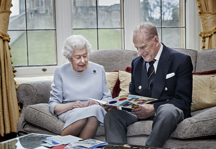 The beautiful image features The Queen and Philip looking at a card made by their great gradnchildren.