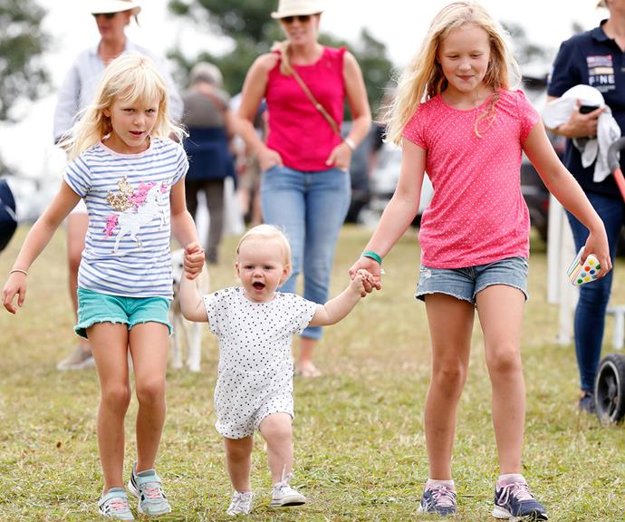 Gang's all here! Older cousins Isla and Savannah Phillips hold their baby cousin Lena's hands at the 2019 Festival of British Eventing at Gatcombe Park.