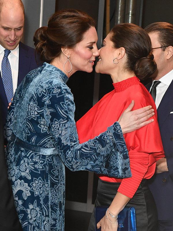Duchess Catherine and Princess Victoria share a warm kiss hello.