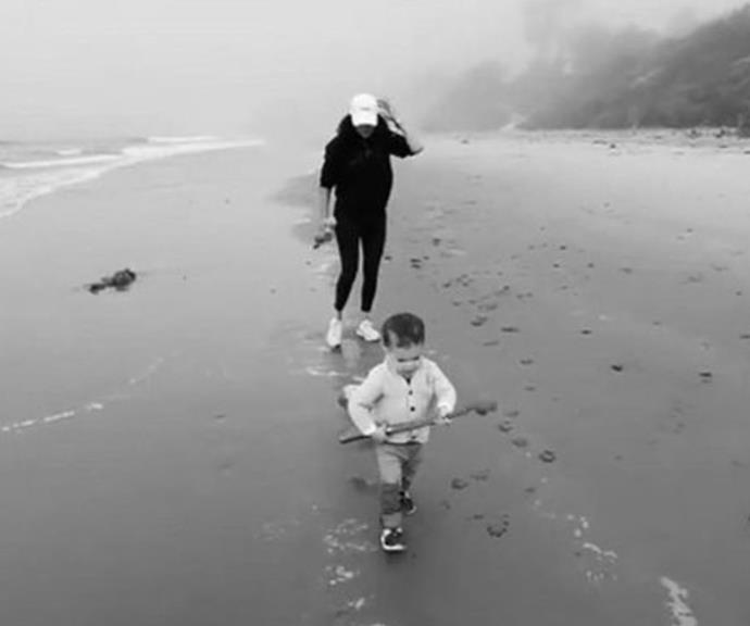 Beach bliss: Archie races between his mum and dad on the shoreline.
