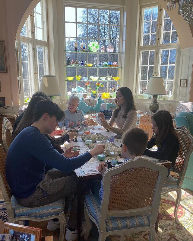 The family sat together in the sun-drenched room to paint Easter eggs.
