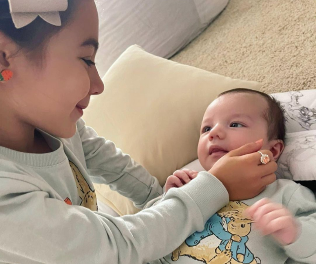 We're just melting over this precious moment between new siblings - look at that loving gaze!