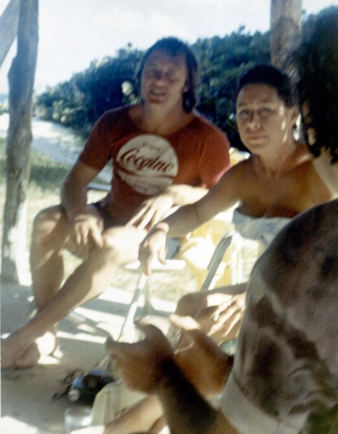 """Margaret poses with John – who is wearing a T-shirt with the slogan """"Enjoy Cocaine"""" – in Mustique."""