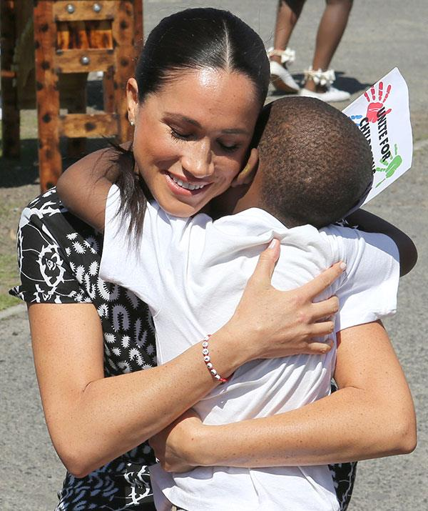 Duchess Meghan embraces a young boy during a visit to Cape Town, South Africa in 2019.