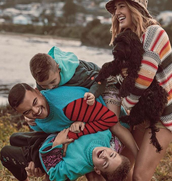 The family having a winter beach side laugh wearing the coolest jumpers.