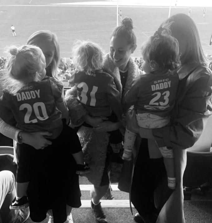 The girls at the footy supporting dad!