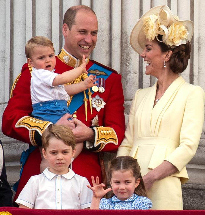 Little Louis in Will's arms, while Kate Middleton laughs at them and Charlotte and George look down from the balcony.