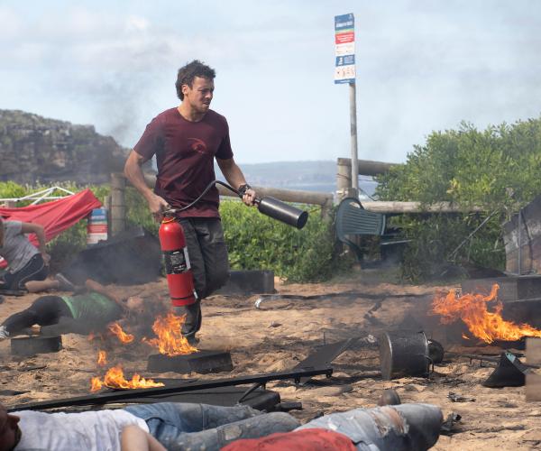Dean desperately battles the flames.