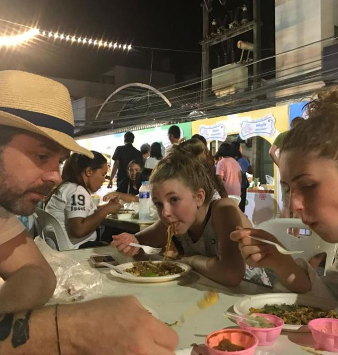 Jock eating at a food market with his older daughters.