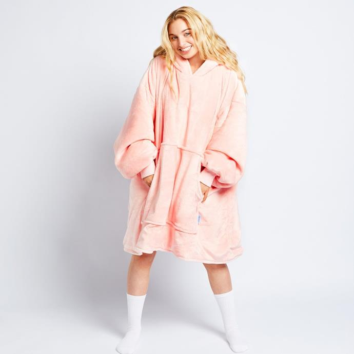 """This fluffy pink Oodie will listen to your work stories and watch reruns of *Sex and the City* with you whenever you want. $109, **[buy it online here](https://theoodie.com/products/pink-blanket-hoodie target=""""_blank"""" rel=""""nofollow"""")**"""
