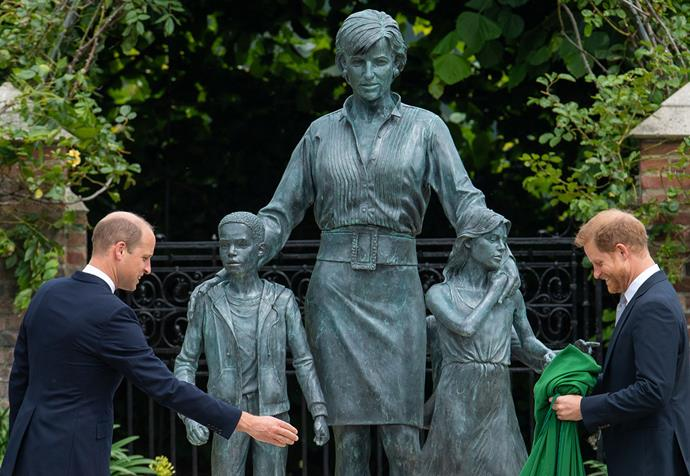 The bronze statue of the late Princess Diana shows her with her arms around two young children, with a third child in the background.