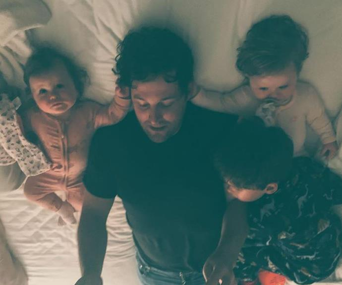 """Lachy surrounded by his children as they attempt to find Spot together, and the way his twin girls are holding his hair is simply too cute. Lachy captioned the post, """"It takes a village to find Spot 🐶."""""""