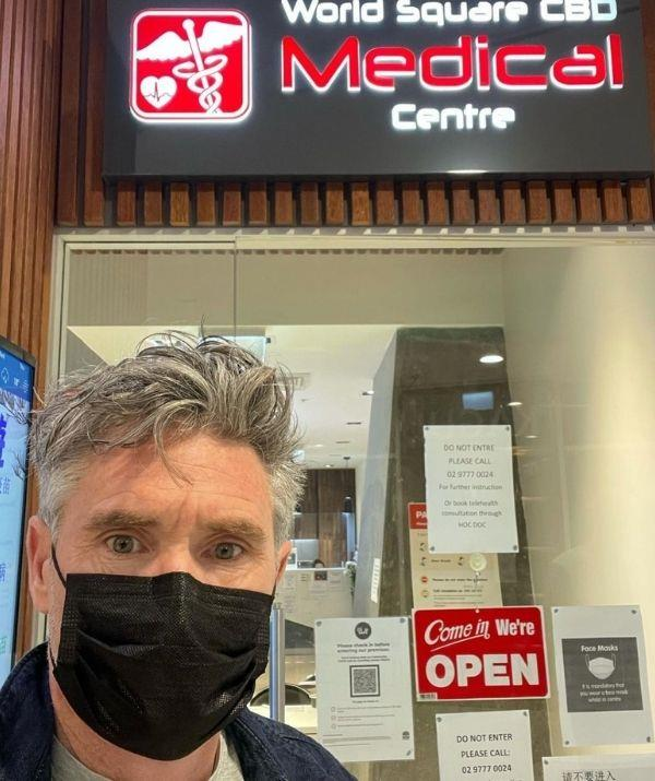 """**Dave Hughes** <br><br>  Radio host Dave 'Hughesy' Hughes has finally joined the fully vaccinated club. The funnyman marked the milestone occasion with a picture in front of the medical clinic that gave him his jab.  <br><br> Hughesy captioned the moment, """"2nd AstraZeneca jab done. Fully vacced!"""""""
