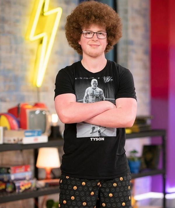 **Sam: Before** <br><br> Sam's iconic Napoleon Dynamite fro was welcomed as an iconic addition to Beauty and the Geek. A lover of statement T-shirts and patterned shorts, Sam's always been confident.