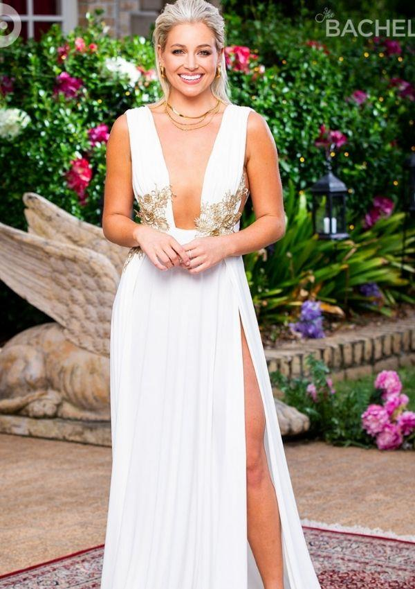 Holly wore this plunging white dress with a risqué thigh-high side slit for her second rose ceremony. The outfit avoids looking like any old white dress by featuring gold adornments around the bodice. Holly expertly styled the look with three simple gold necklaces and earrings, which created a cohesive aesthetic.