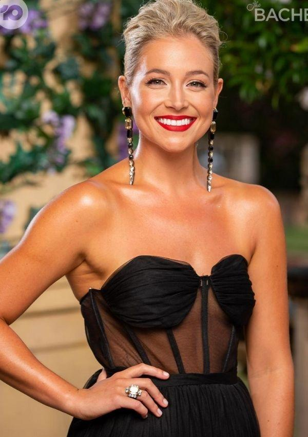 We are obsessed with Holly's classy but modern gown, with a heart-shaped neckline accentuated by transparent panels around the bodice. In addition, the unique art-deco earrings are a vintage dream.