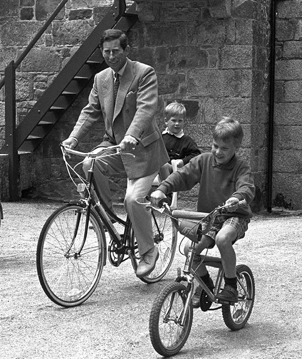 This picture from 1989 shows William riding ahead of his father, while Harry rides on the back of Charles' bike during a family holiday on Tresco, Scilly Isles.
