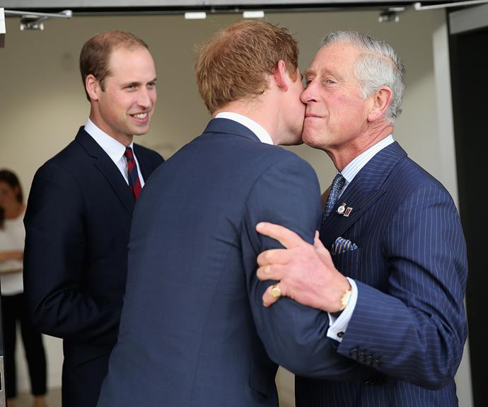 Prince Harry greets his father with a kiss while Prince William smiles.