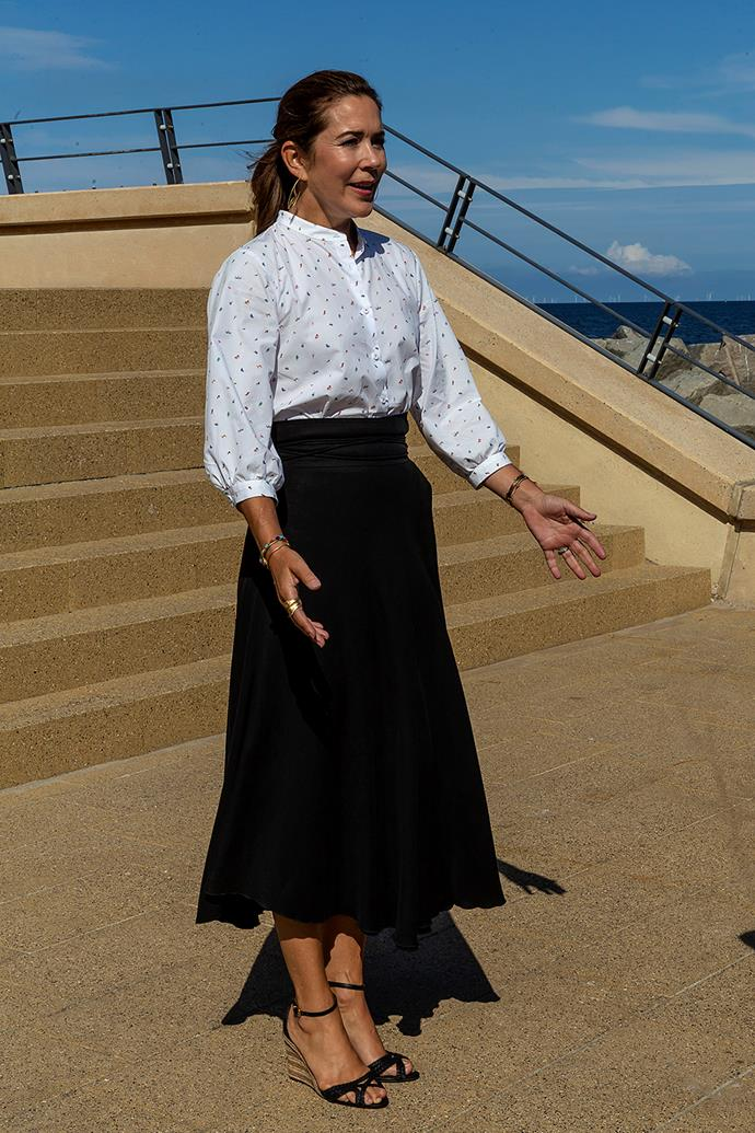 **August 2020, Denmark** <br><br> For an August engagement by the sea, the princess wore the classic combination of a black skirt and white blouse. She mixed it up by wearing a shirt with small puff sleeves and a delicate pattern across it, opting for black wedge sandals over her usual closed-toe pumps.