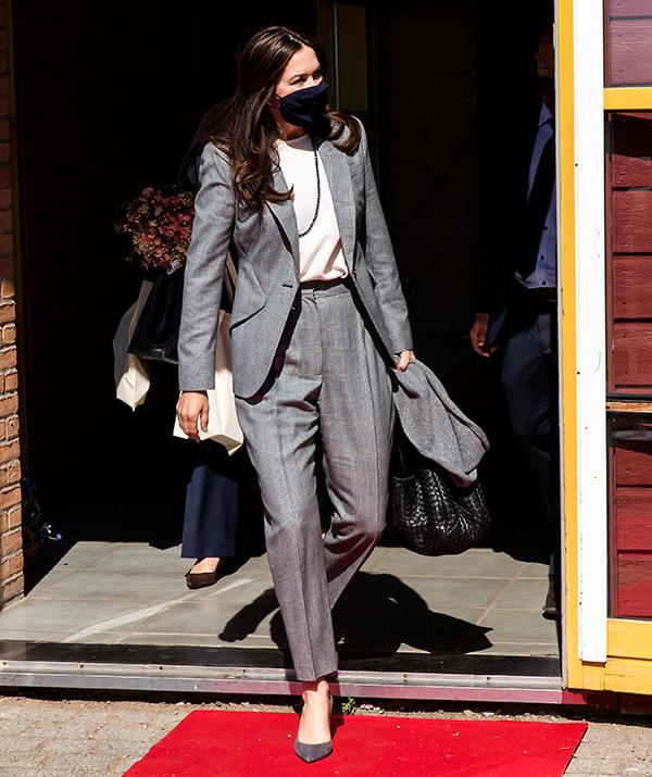 **April 2021, Denmark** <br><br> The Crown Princess donned this chic tailored pantsuit for a visit to the UNFPA State Of World Population Report Release in April, 2021 in Denmark. She paired her menswear-inspired ensemble with grey point-toe pumps, a long necklace and - of course - a face mask to complete her look.