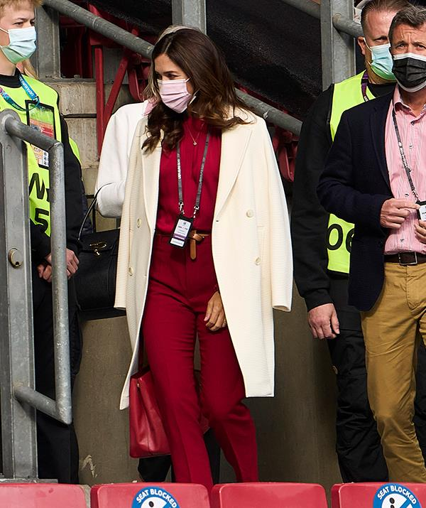 **June 2021, Denmark** <br><br> Mary showed us the power of a monochromatic look at a UEFA EURO 2020 match between Denmark and Finland in June. Pairing a red Hugo Boss blouse with a pair of slacks in the same shade and a matching bag, Mary set off the all-red look with a chic cream coat.