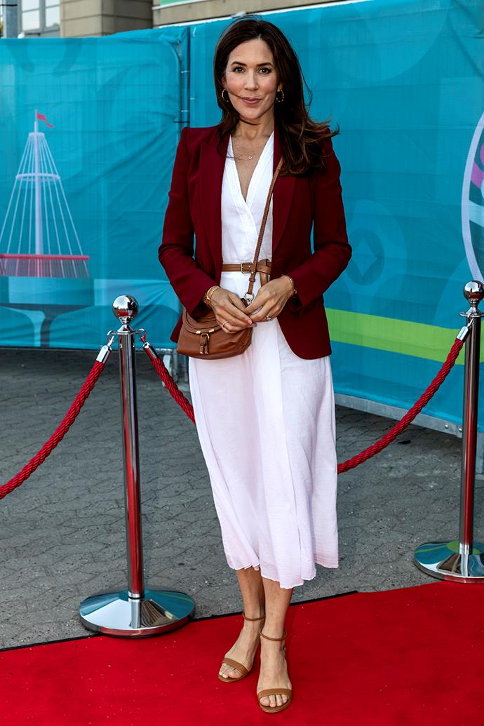 **June 2021, Denmark** <br><br> For a second soccer match in June, Mary flipped her look, opting for a casual white dress and luxe Alexander McQueen blazer, topping it off with a brown bag by Chloe. She tied the look together with simple brown accessories, including a thin belt and heeled sandals.