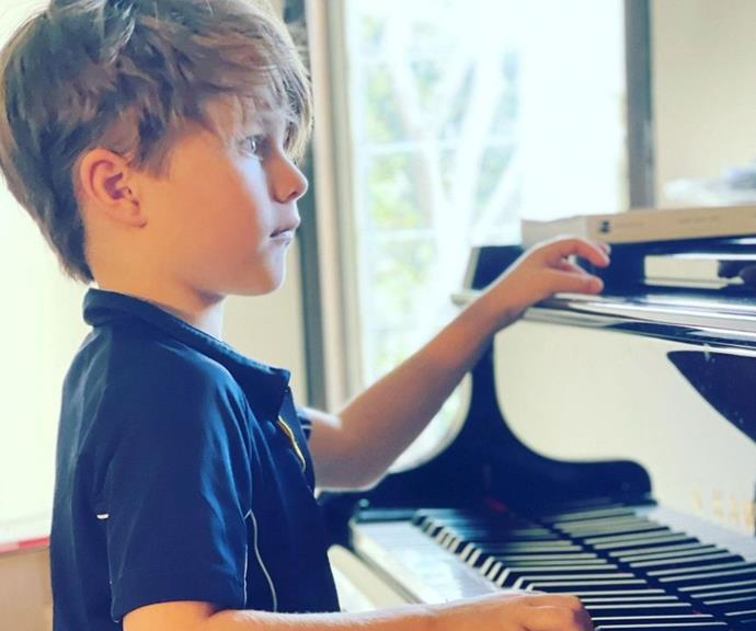 """David posted this picture of his younger son Billy playing the piano in Sydney's lockdown.  <br><br> The proud dad captioned the image, """"Billy. He won't let us cut his hair and now he is teaching himself piano by an app. He living his lockdown best. #billy."""""""