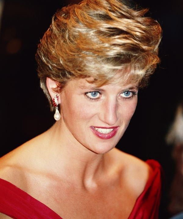 **Princess Diana** <br><br> Diana is best known for her dark eyeliner, but she also loved a nude and subtle red lip. In this look, her cherry red lipstick features brown undertones, which matches the red in her earrings and dress. It's perfect for those who want to start playing with reds.