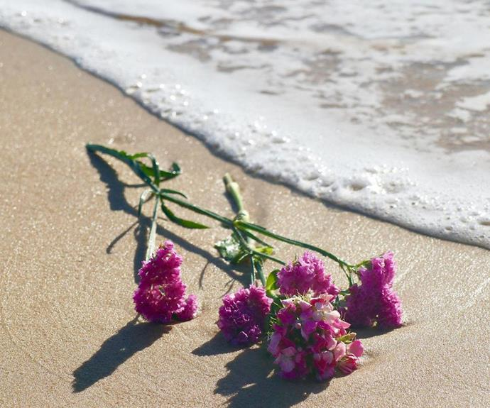 """Jaimi's close friend concluded her tribute with several photos of colourful flowers lying on the sand, writing: We filled the ocean with pretty flowers for you + I could feel you looking down on all of us + smiling your gorgeous smile. You are so loved + missed my darling girl; more than you can begin to imagine."""""""